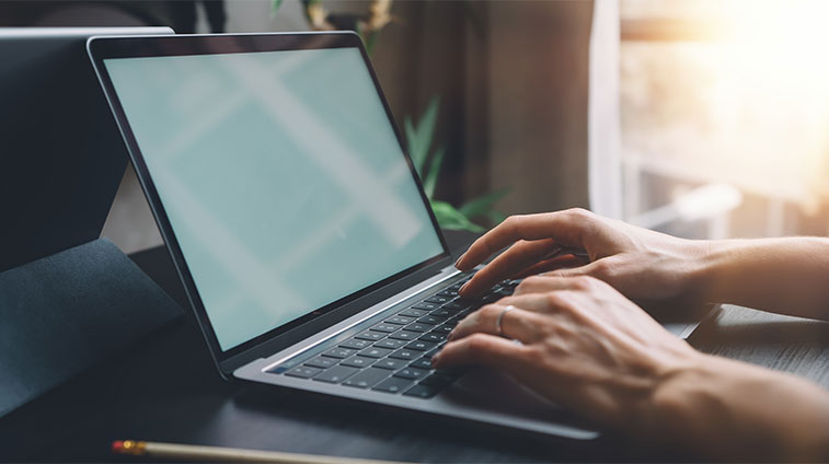 Woman Typing Letter on Laptop
